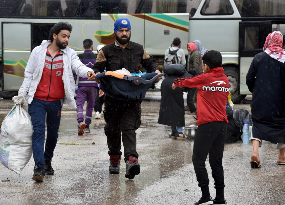 The fourth convoy carrying civilians depart from the Free Syrian Army (FSA) controlled area of Yarmouk Camp in southern Damascus under the Yarmouk camp evacuation agreement, as part of the compulsory evacuation as agreed on April 29, in Damascus, Syria on 7 May, 2018 [Muhammed Abdullah/Anadolu Agency]