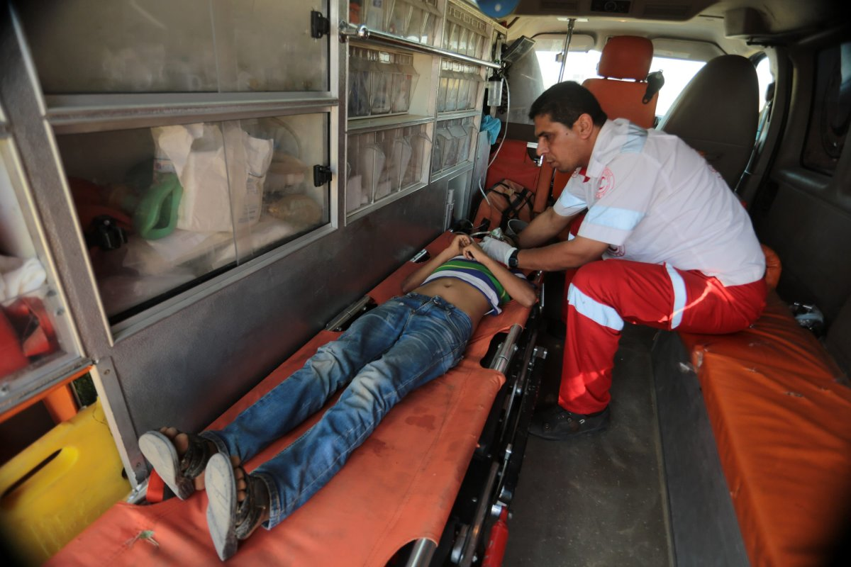 A Palestinian receives medical treatment after Israeli occupation forces' intervention during a protest, organized to mark 70th anniversary of Nakba, also known as Day of the Catastrophe in 1948, and against United States' plans to relocate the U.S. Embassy from Tel Aviv to Jerusalem, near Israel border in Khan Yunis, Gaza on 16 May, 2018 [Abed Rahim Khatib/Anadolu Agency]