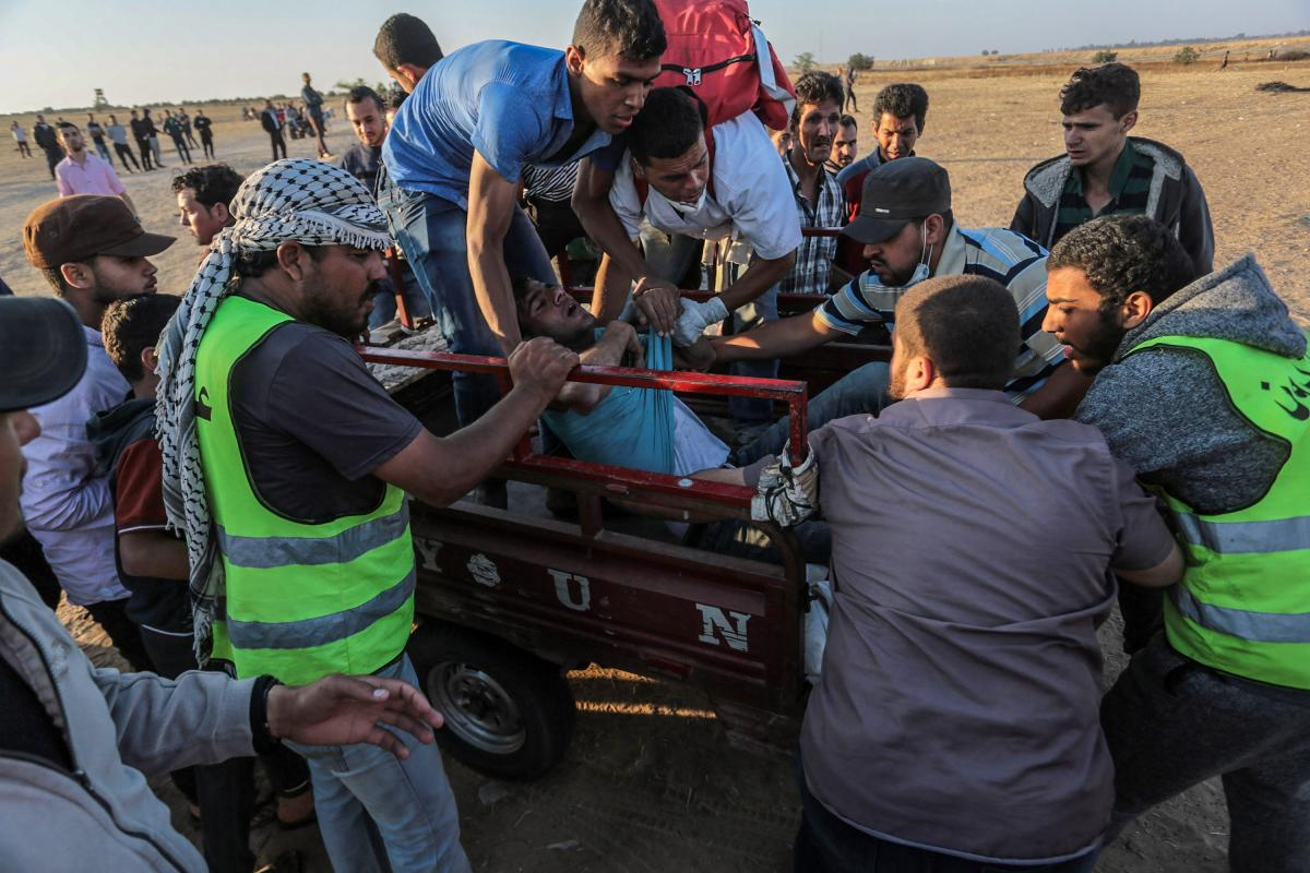 Palestinians carry a wounded man to ambulance after Israeli occupation forces' intervention during a protest, organized to mark 70th anniversary of Nakba, also known as Day of the Catastrophe in 1948, and against United States' plans to relocate the U.S. Embassy from Tel Aviv to Jerusalem, near Israel border in Khan Yunis, Gaza on 16 May, 2018 [Abed Rahim Khatib/Anadolu Agency]