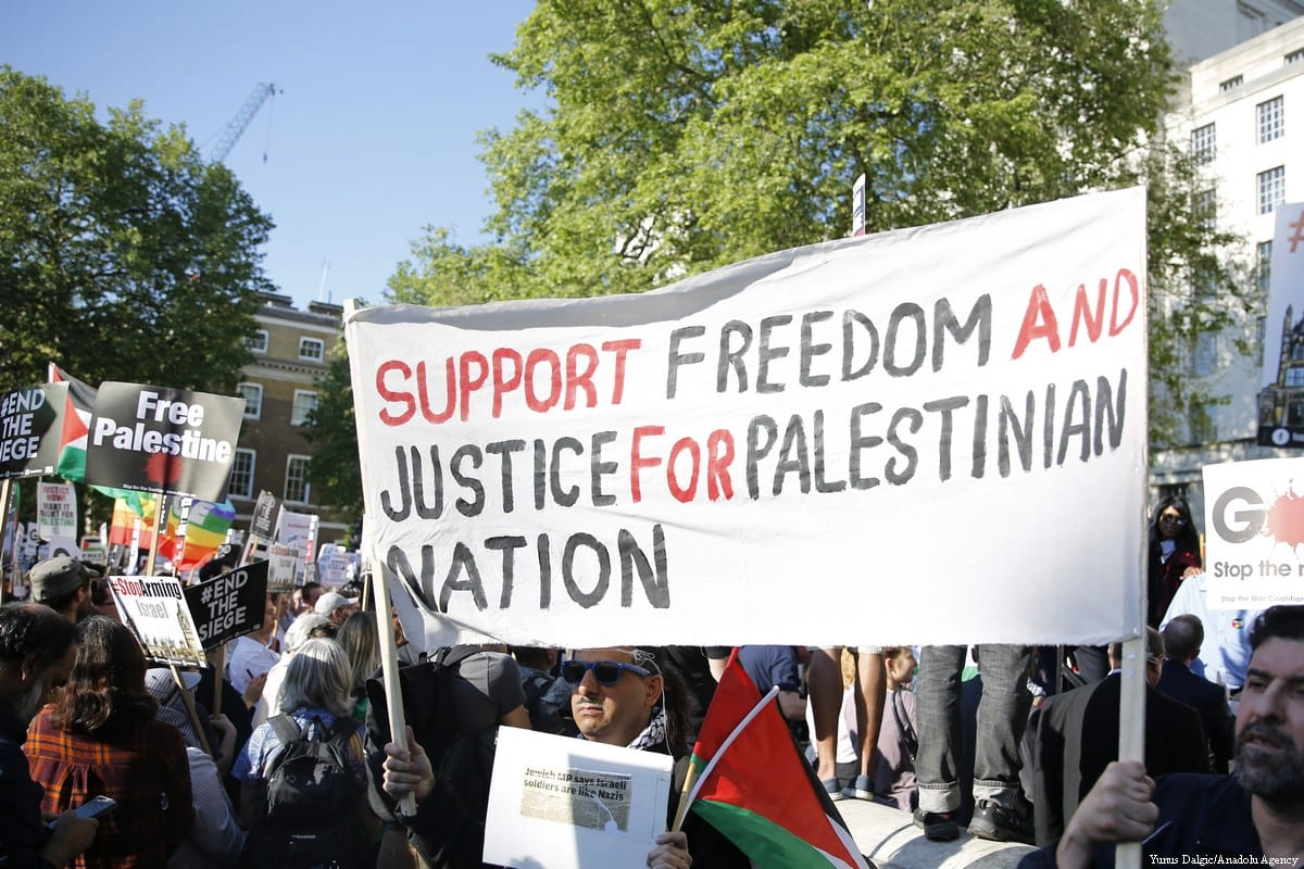 Pro-Palestine demonstrators hold placards during a protest against Israel's treatment of Palestinian protesters in London, UK on 15 May 2018 [Yunus Dalgic/Anadolu Agency]