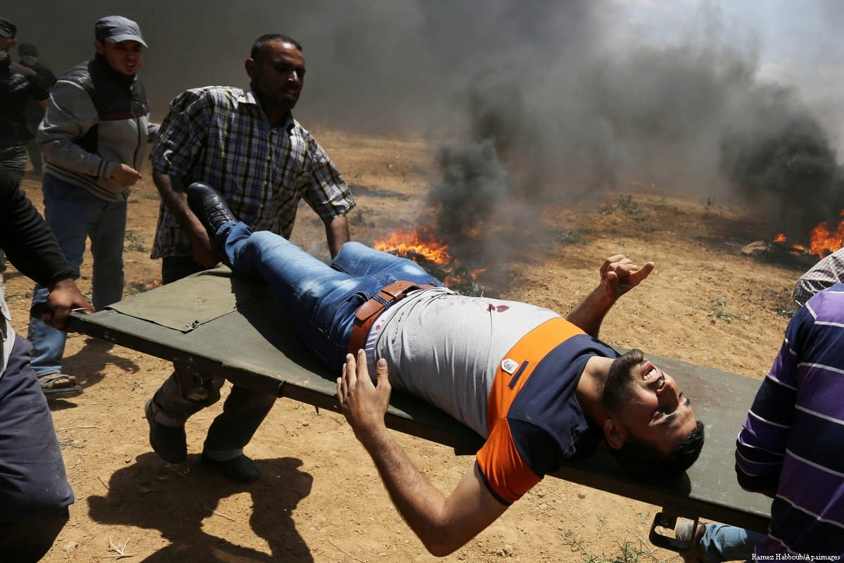 """A wounded Palestinian protester is evacuated during clashes with Israeli security froces in a tent city protest where Palestinians demand the right to return to their homeland, on the occasion of the 70th anniversary of the """"Nakba"""", and against U.S. embassy move to Jerusalem at the Israel-Gaza border, in Khan Younis in the southern Gaza Strip on 14 May, 2018 [Ramez Habboub/Apaimages]"""