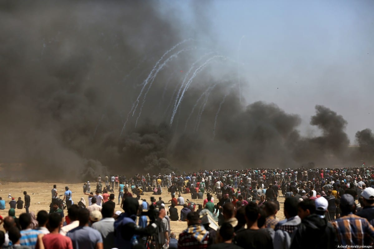 "Palestinian protesters gather during clashes with Israeli security forces in a tent city protest where Palestinians demand the right to return to their homeland, on the occasion of the 70th anniversary of the ""Nakba"", and against U.S. embassy move to Jerusalem at Israel-Gaza border at the Israel-Gaza border, in east of Gaza city on 14 May, 2018 [Ramez Habboub/Apaimages]"