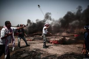 "Palestinians use slingshot to throw stones during the protests called ""commemorating the Naksa"", along the border fence, east of Khan Yunis in the southern Gaza Strip on June 8, 2018 [Mustafa Hassona / Anadolu Agency]"