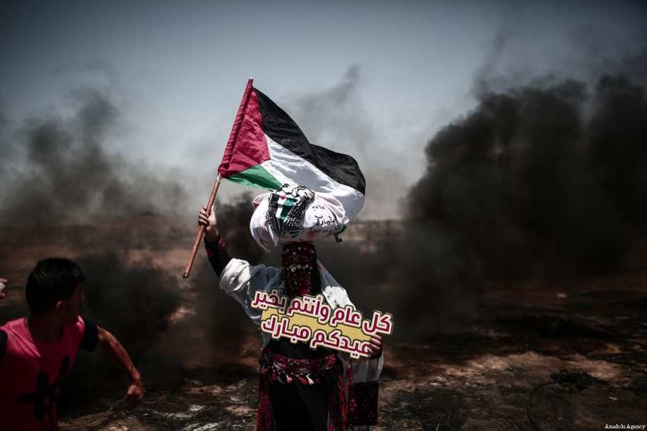 """Palestinian holds a banner reading """"Eid Mubarak"""" as they burn tyres in response to Israeli security forces' intervention during the protests called """"commemorating the Naksa"""", along the border fence, east of Khan Yunis in the southern Gaza Strip on June 8, 2018 [Mustafa Hassona / Anadolu Agency]"""