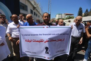 Palestinians protest outside UNRWA against cuts and changes to work conditions in Gaza on 25 June 2018 [Mohammed Asad/Middle East Monitor]
