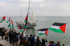 crowds gather at Brighton Marina wall to welcome 'Freedom' boat to Gaza as it sails past [Jehan Alfarra/Middle East Monitor]