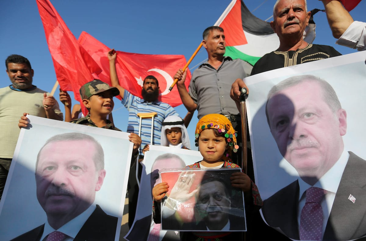 Palestinians hold portraits of Turkish President Recep Tayyip Erdogan during a rally to support with Turkey's presidential and parliamentary elections in Al-Bureij in the center of Gaza Strip on 24 June, 2018 [Ashraf Amra/Apaimages]