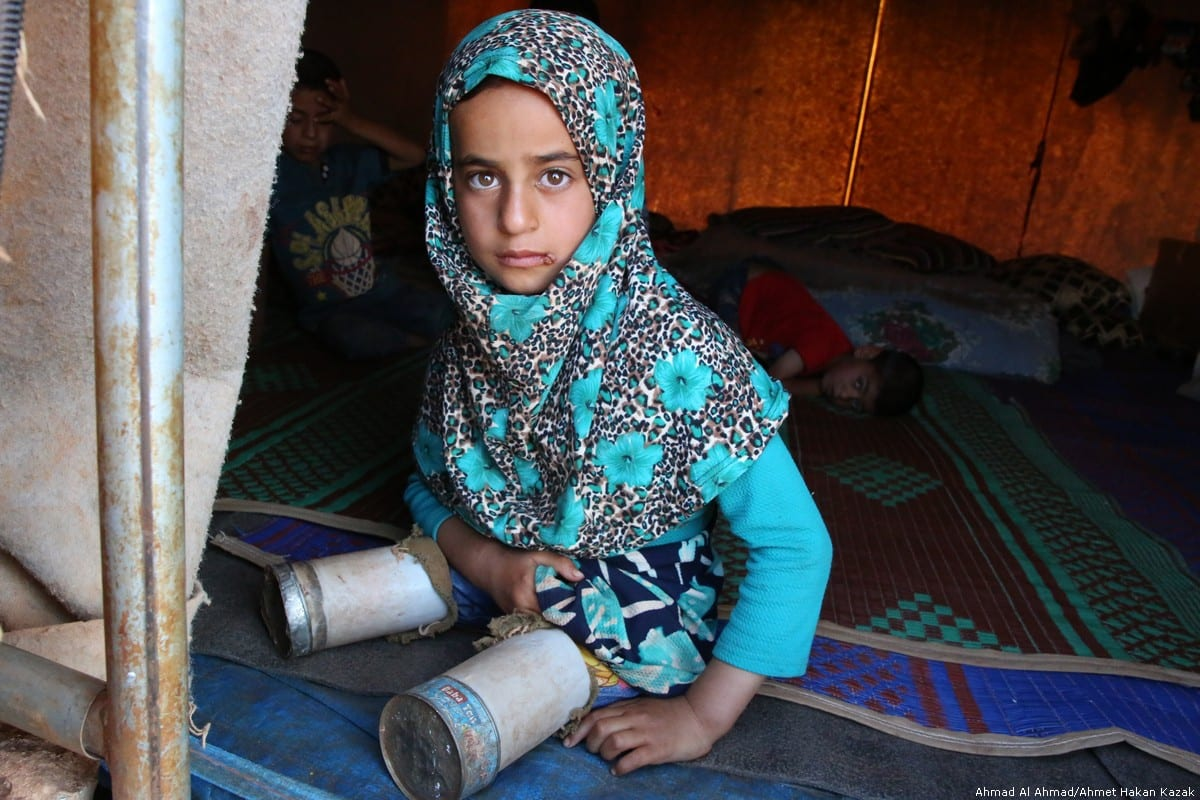 Syrian Maya Meri (8) is seen with her artificial legs, made from tin cans in Idlib, Syria on 21 June 2018 [Ahmad Al Ahmad/Anadolu Agency]