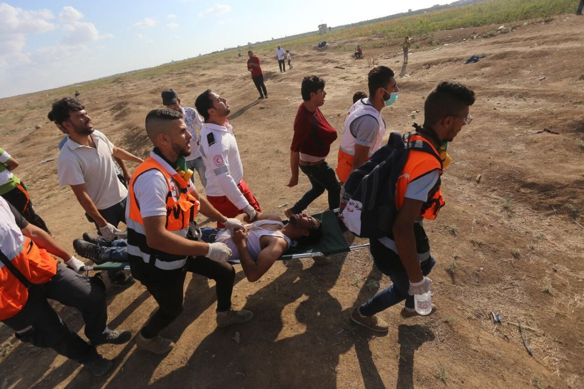 Palestinians carry an injured protester after Israeli forces fired tear gas at protesters during the Great March of Return Muhammad Asad]