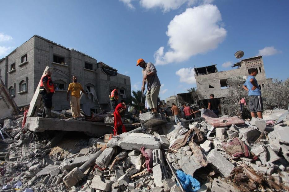Rescue workers search for victims after air strikes hit Gaza during the 2014 Israeli offensive against Gaza [Ashraf Amra/Apaimages]