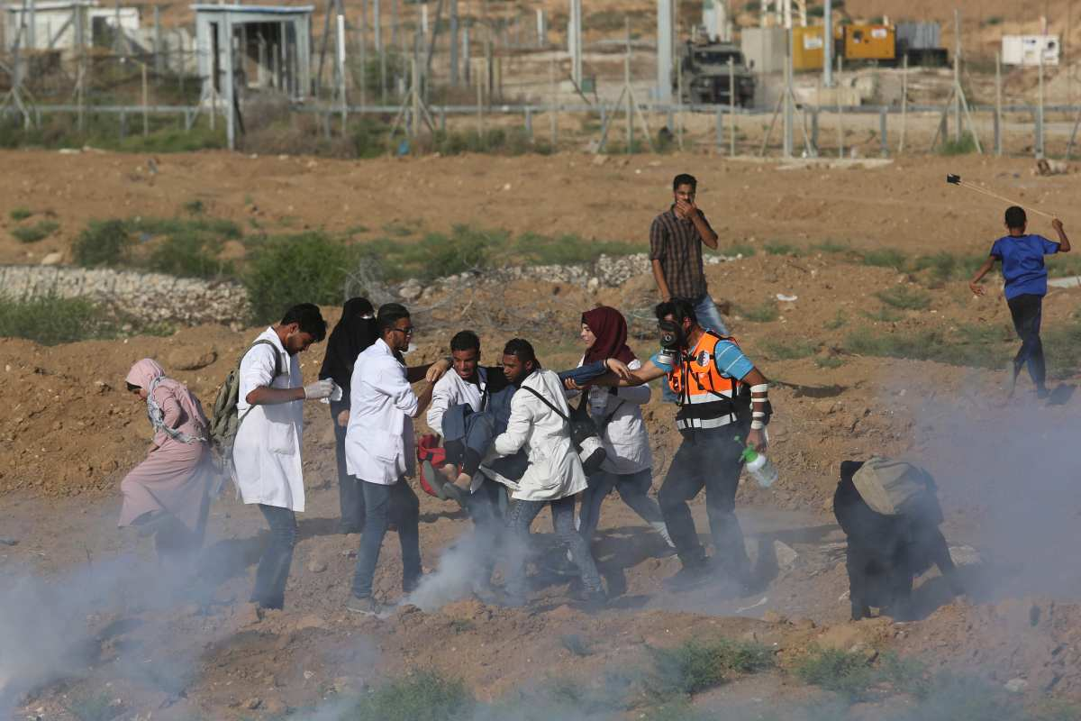 """Palestinian medical staff carry a wounded woman during a protest within the """"Great March of Return"""" demonstrations near Israel-Gaza border in Gaza City, Gaza on 3 July, 2018 [Ashraf Amra/Anadolu Agency]"""