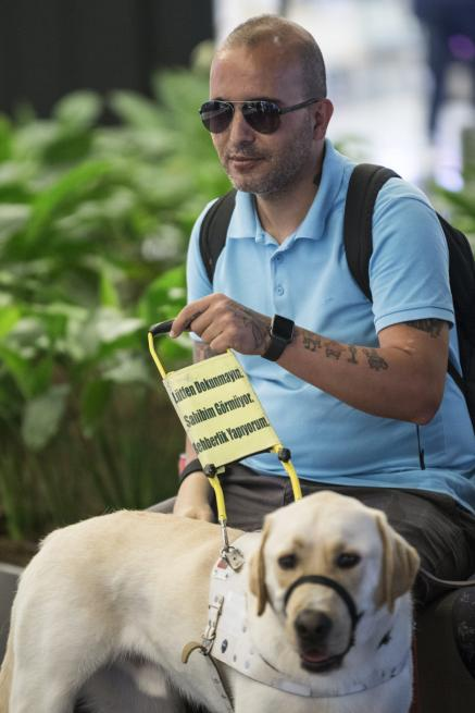Veteran Gendarmery Sergeant Hasan Arisoy (L), who lost his sight ability and his right hand after a mine bomb blasted in Cukurca, is seen with his guide dog Labrador Retriever Bobby (R) with the help of trainer of guide dog and mobility Kubra Demirkaya (not seen) during adaptation process in Istanbul, Turkey on 3 July, 2018 [Orhan Akkanat/Anadolu Agency]