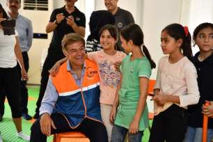Turkish-American cardio-thoracic surgeon Mehmet Oz (C) meets with Syrian refugees during his visit to Gaziantep, Turkey on 8 July 2018 [Kerem Kocalar/Anadolu Agency]