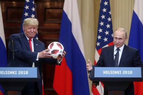 U.S. President Donald Trump (L) holds official FIFA World Cup 2018 ball presented by Russia's President Vladimir Putin (R) during a joint press conference after their bilateral meeting in Helsinki, Finland on 16 July, 2018 [Stringer/Anadolu Agency]