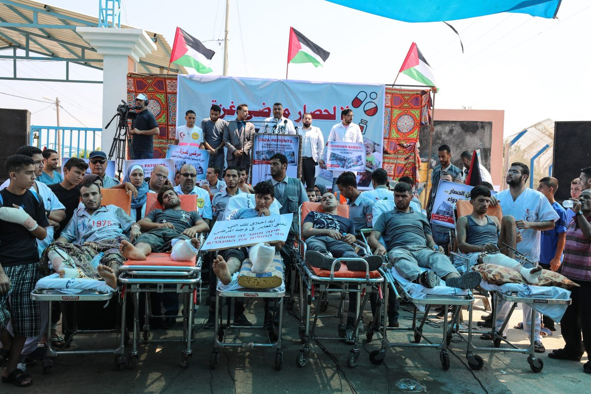 First aid crews and patients lying on stretchers take part in a protest against the impairment of health due to Israel's over a decade long blockade in front of Beit Hanoun Border Gate in Gaza City, Gaza on 17 July, 2018 [Mustafa Hassona/Anadolu Agency]