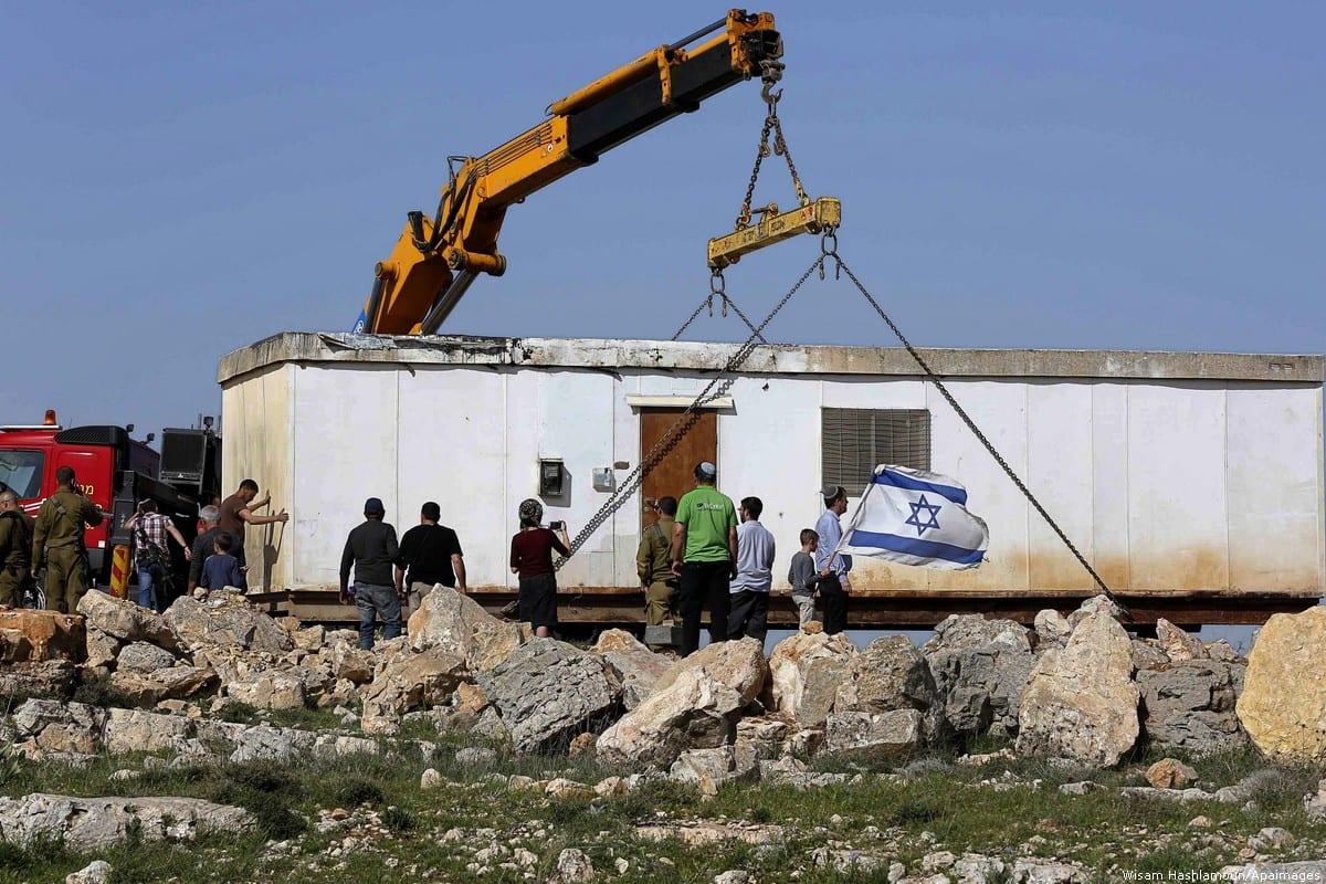 A construction crane installs new mobile homes on Palestinian land near Kiryat Arba settlement in Hebron, West Bank on 5 March 2018 [Wisam Hashlamoun/Apaimages]