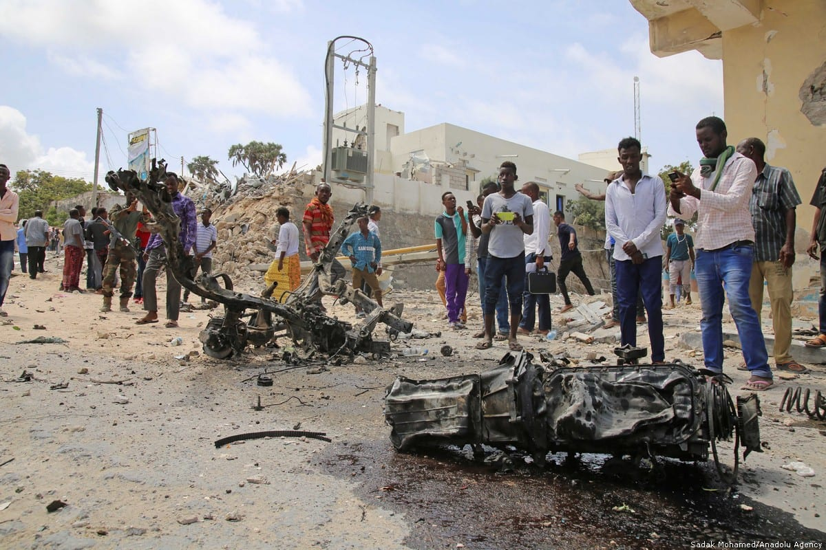 People gather around the wreckage of a suicide car bomb that detonated at a security checkpoint in Somalia [Sadak Mohamed/Anadolu Agency]