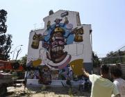 A mural depicting a cartoon graffiti spray can on the facade of a building [Veli Gürgah/Anadolu Agency]