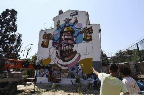 A mural depicting a cartoon graffiti spray can on the facade of a building [Veli Gürgah/Anadolu Agency]