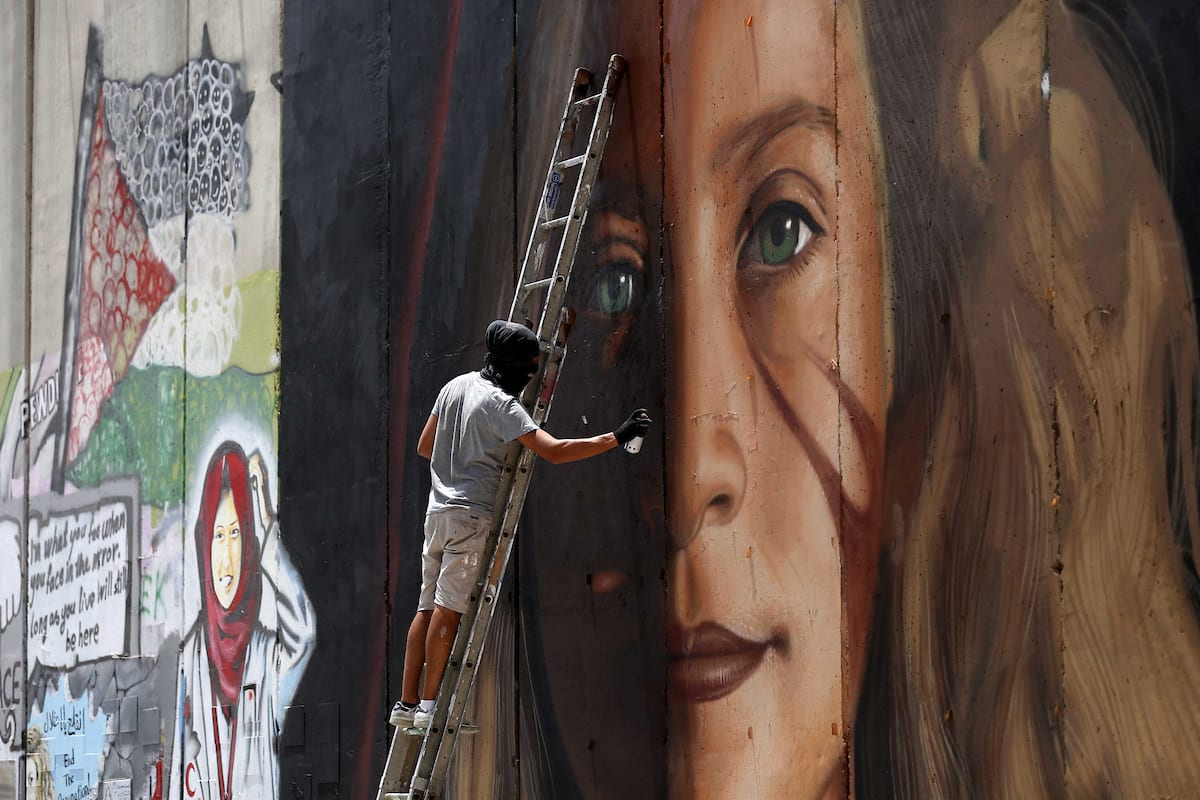 Italian artist Jorit Agoch paints a mural depicting Palestinian teenager Ahed Tamimi on Israel's controversial separation barrier in the West Bank city of Bethlehem, on 25 July,2018 [ Wisam Hashlamoun/Apaimges]