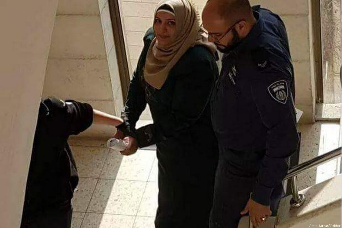 Fadwa Nazih Kamel Hamada can be seen taking into custody by Israeli police [Amin Jarrar/Twitter]