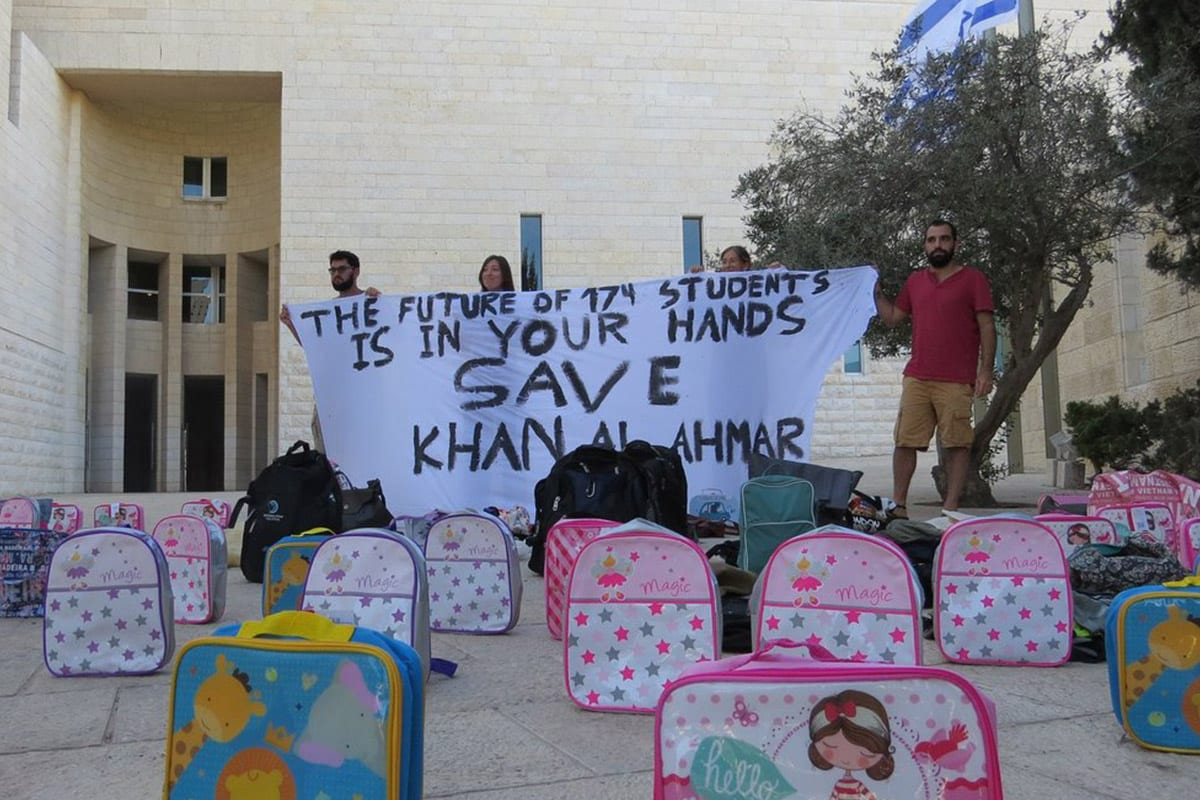 Anti-occupation activists brought 174 school backpacks to Israel's Supreme Court to symbolize the 174 children who would lose their school if the Israeli army destroys Khan Al-Ahmar, a Palestinian Bedouin Village. [Facebook/All That's Left: Anti-Occupation Collective]