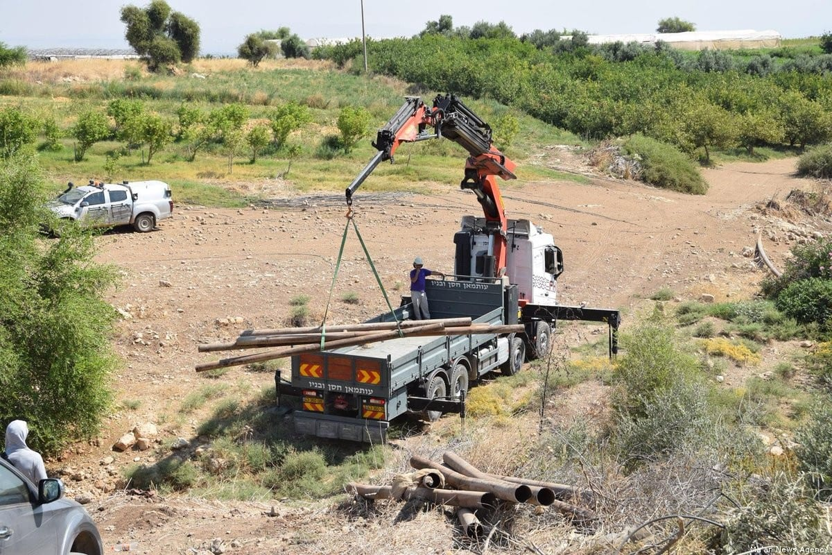 Israeli forces can be seen confiscating water pipes in the Jordan Valley [Ma'an News Agency]