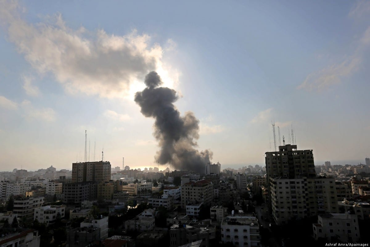 Smoke rises above buildings during an Israeli air strike on Gaza City on 14 July 2018 [Ashraf Amra/Apaimages]