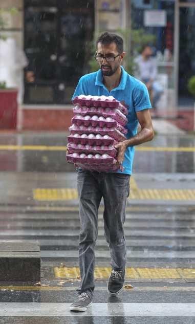 A man carries eggs as torrential rain hits Ankara, Turkey on 31 July, 2018 [Celal Güneş/Anadolu Agency]