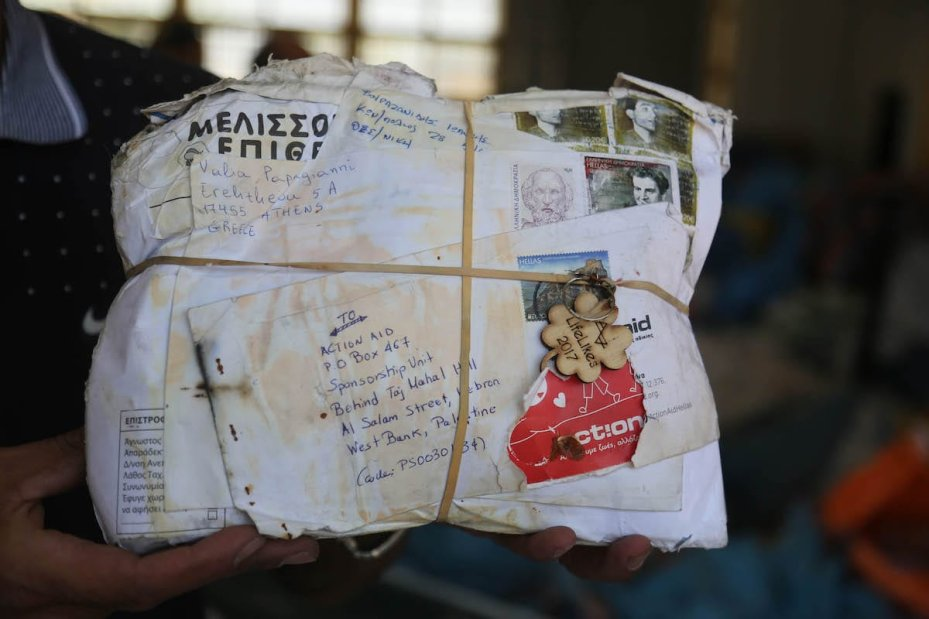 Palestinian postal worker shows an undelivered mail blocked by Israel for years at the Palestinian central international exchange post office in Jericho, West Bank