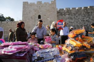 Families buying toys for their children after the Salat al Eid prayer at the Al-Aqsa mosque compound during the first day of the Eid Al Adha in Jerusalem on 21 August, 2018 [Mostafa Alkharouf/AnadoluAgency]