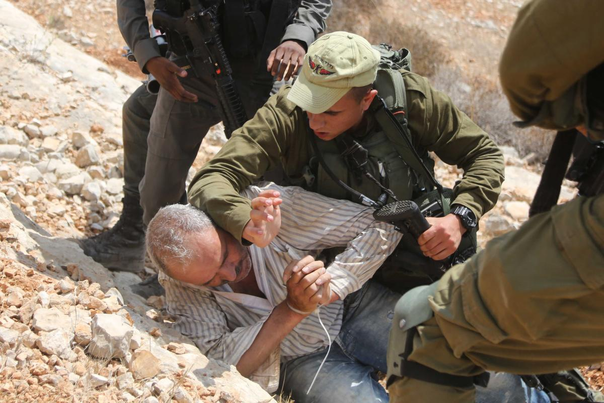 Israeli forces hold down a Palestinian man in Ramallah, West Bank on 28 August 2018 [Issam Rimawi/Anadolu Agency]