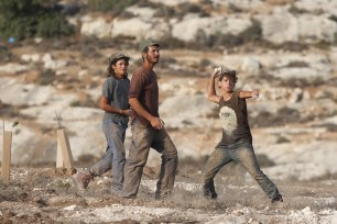 Palestinian protesters throw rock in response to Israeli intervention during a demonstration held against Jewish occupation over Palestinians' fields in Ras Karkar village of Ramallah, West Bank on 30 August, 2018 [Issam Rimawi/Anadolu Agency]