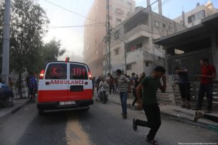 Ambulances rush to help injured Palestinians after Israeli occupation forces targeted a cultural centre in Gaza [Mohammed Asad/Middle East Monitor]