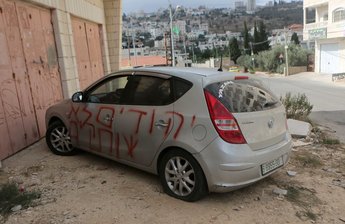 """Settlers sprayed racist slogans that read in Hebrew """"Jews will not be silent"""" and slashed the tyres of a Palestinian resident's car in the occupied West Bank town of Singel north of Ramallah, on 27 August, 2018 [Shadi Hatem/Apaimages]"""