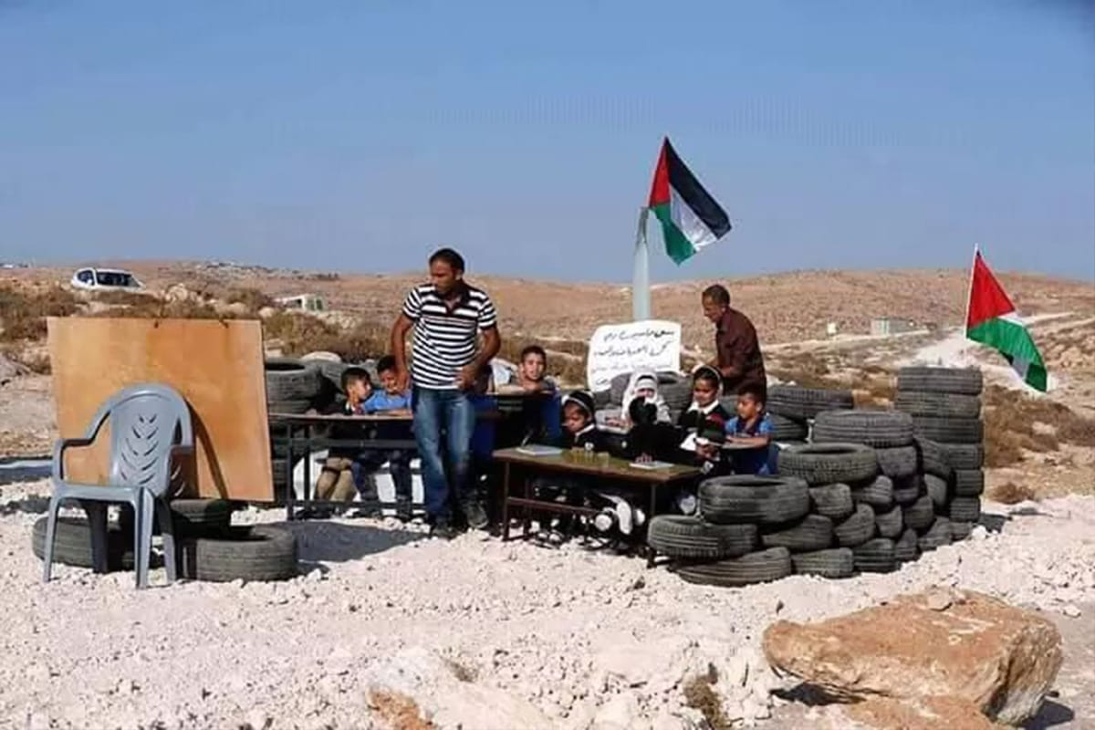 After Israeli forces demolished their school building, Palestinian students and teachers can be seen at a makeshift school