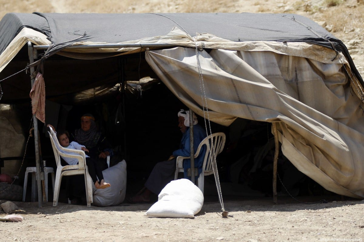 Palestinians can be seen inside a tent after they were evicted from their homes in the Jordan valley by Israeli forces due to military training [Shadi Hatem/Apaimages]