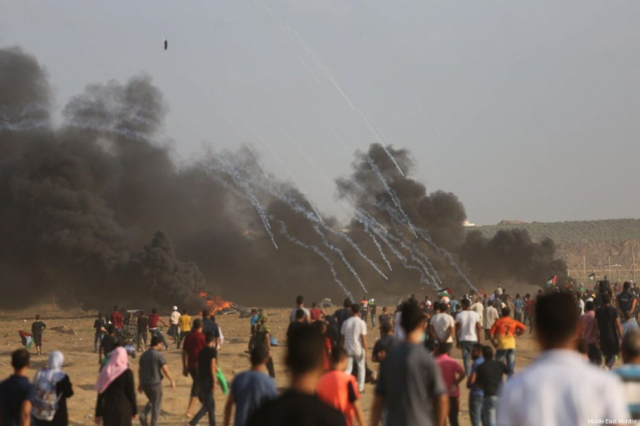 "A Palestinian-launched ""incendiary device"" [balloon or kite] can be seen in the top-right, as Israeli forces shower Palestinians in a hail of tear gas, at the Gaza-Israel border, gathered as part of the continuing 'Great March of Return' on August 3, 2018 [Mohammad Asad / Middle East Monitor]"