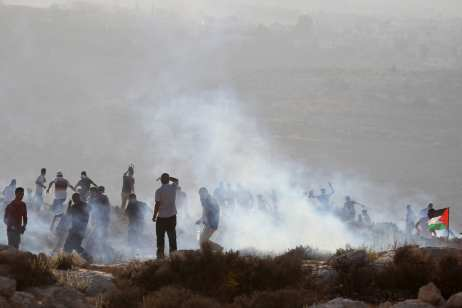 Palestinians run away from tear gas fired by Israeli forces to disperse a protest, held against Israeli settlement construction on Palestinians' fields, in the village of Ras Karkar near Ramallah, West Bank on 4 September, 2018 [Issam Rimawi/Anadolu Agency]