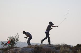 A Palestinian uses a slingshot to throw stones in response to Israeli forces' intervention during a protest against Israeli settlement construction on Palestinians' fields, in the village of Ras Karkar near Ramallah, West Bank on 4 September, 2018 [Issam Rimawi/Anadolu Agency]