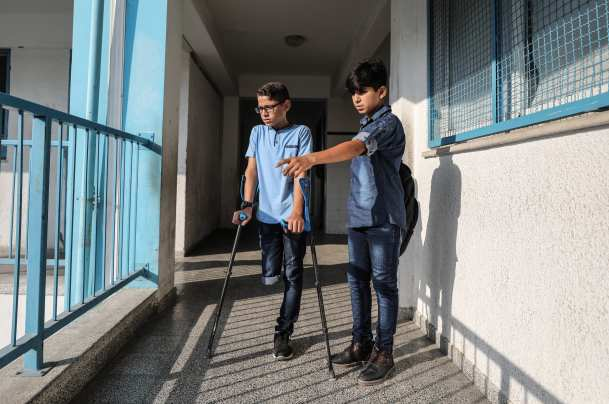 """Palestinian student Mohammed Abu Hussain from Gaza, who lost his leg after being shot by an Israeli sniper during """"Great March of Return"""" demonstrations, arrives his school with his crutches in Gaza City, Gaza on September 03, 2018. ( Ali Jadallah - Anadolu Agency )"""