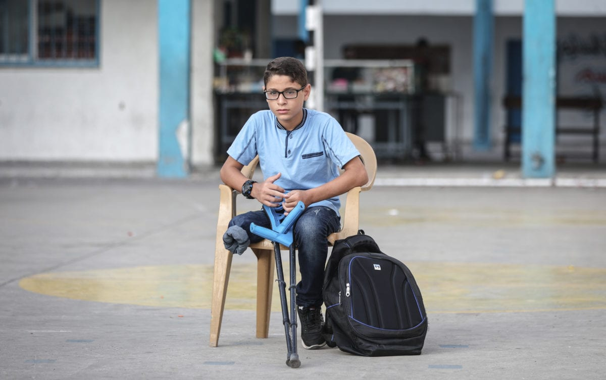 "Palestinian student Mohammed Abu Hussain from Gaza, who lost his leg after being shot by an Israeli sniper during ""Great March of Return"" demonstrations, sits on a chair holding his crutches at the playground of his school in Gaza City, Gaza on 3 September 2018. [Ali Jadallah - Anadolu Agency]"