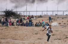 """Palestinians run away after Israeli intervention with tear gas canisters during the """"Great March of Return"""" demonstration at the Israeli border in eastern Deir Al Balah, Gaza on 27 September, 2018 [Mustafa Hassona/Anadolu Agency]"""