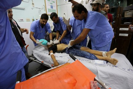 """Palestinian paramedics give medical attention to a child after he was shot by Israeli forces during demonstrations at the Israeli border within the """"Great March of Return"""", at the European Hospital in Khan Yunis, Gaza on September 28, 2018. ( Ashraf Amra - Anadolu Agency )"""