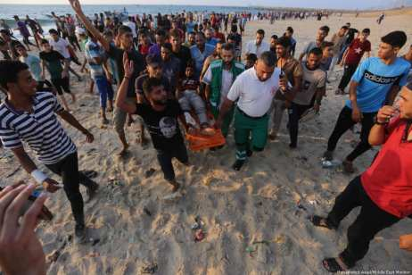 Palestinians carry a wounded protester after Israeli naval ships fired gas canisters and shot at demonstrators in Gaza's coastal waters [Mohammed Asad/Middle East Monitor]