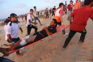 Palestinians carry an injured protester after Israeli forces attacked demonstrators at the Gaza border on 11 September 2018 [Mohammed Asad/Middle East Monitor]