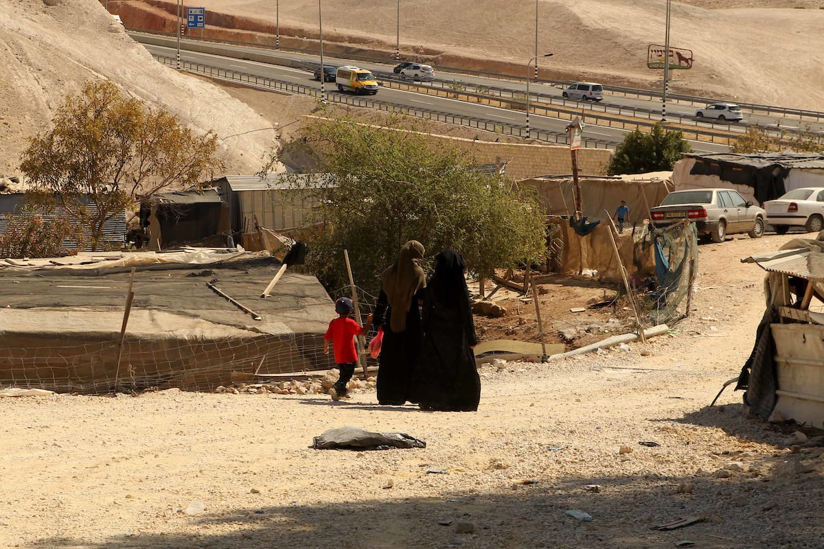 Palestinian Bedouin women walk in the village of Khan al-Ahmar in the Israeli occupied West Bank on 16 September, 2018 [Wisam Hashlamoun/Apaimages]