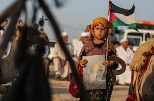 A girl, in traditional clothes, holds a Palestinian flag and a picture of the Kubbat al-Sahra during the Palestinian and Najaf Bedouin Tribes Festival near Gaza border on 2 October, 2018 [Mustafa Hassona/Anadolu Agency]