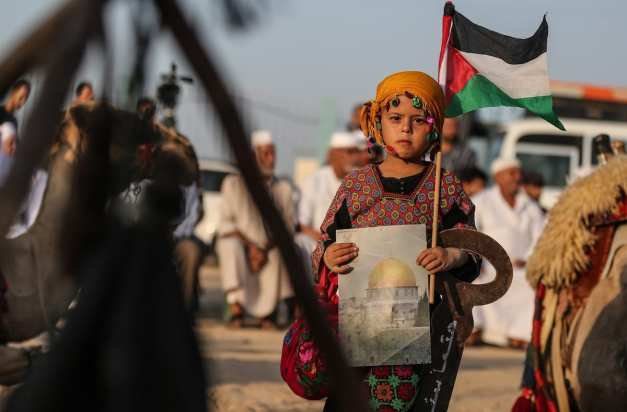 """A girl, in traditional clothes, holds a Palestinian flag and a picture of the Kubbat al-Sahra during the Palestinian and Najaf Bedouin Tribes Festival within the """"Great March of Return"""" demonstrations near Gaza border, in Gaza City, Gaza on 2 October 2018 [Mustafa Hassona/Anadolu Agency]"""