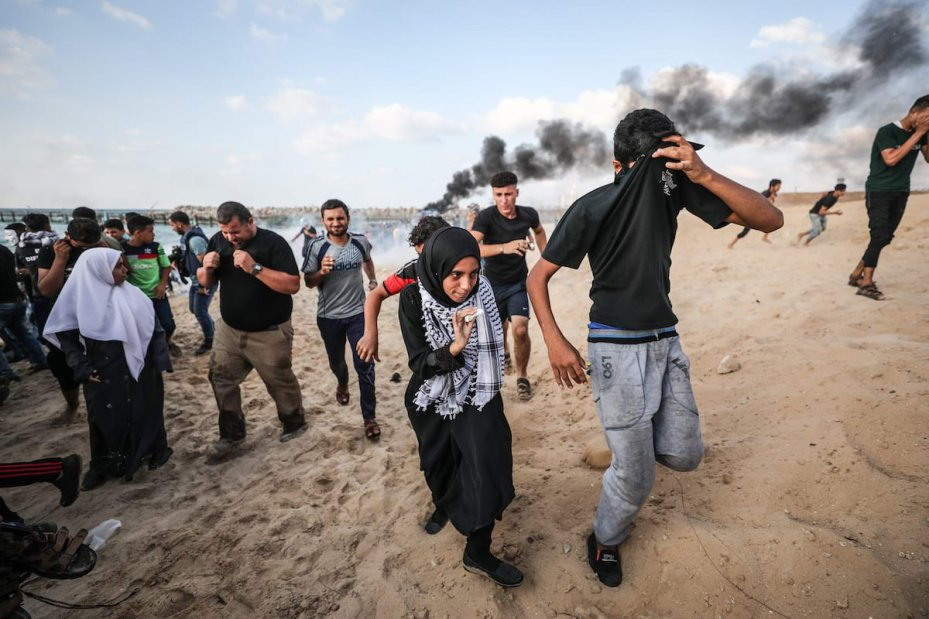 """GAZA CITY, GAZA - OCTOBER 8: Israeli soldiers intervene Palestinians with gas bomb as Palestinians gather to support the """"maritime demonstration"""" to break the Gaza blockade by sea with more than 20 vessels of various sizes in Gaza City, Gaza on October 8, 2018. ( Mustafa Hassona - Anadolu Agency )"""